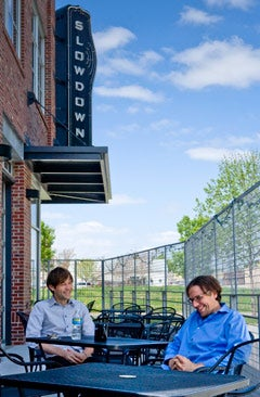 Owners Robb Nansel (above, left) and Jason Kulbel sit outside the Slowdown club (right) in Omaha, Neb., part of a $10 million revitalization effort in the city's industrial corner.