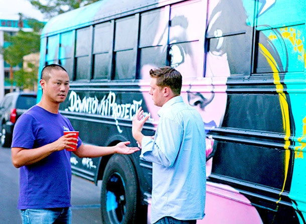 "Zappos CEO Tony Hsieh and Don Welch, who leads the small-business fund, chat before boarding the bus to ""First Friday."""