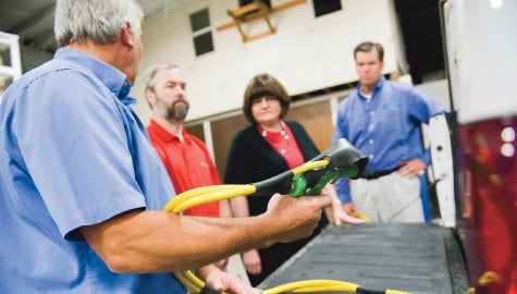 Getting a handle: Bob and Kathy Summers, center, tour Green-Spring Lawn Care Corp. with president James Young, far right.