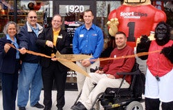 J.J. OConnor, in red, and his business partner Dick Murak (standing next to him, in blue) with fans at the opening of a Sport Clips store.