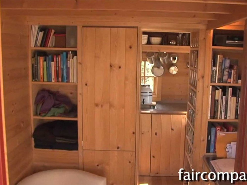 """This 89 square-foot home has an """"entertainment area,"""" a kitchen, and even a fireplace."""