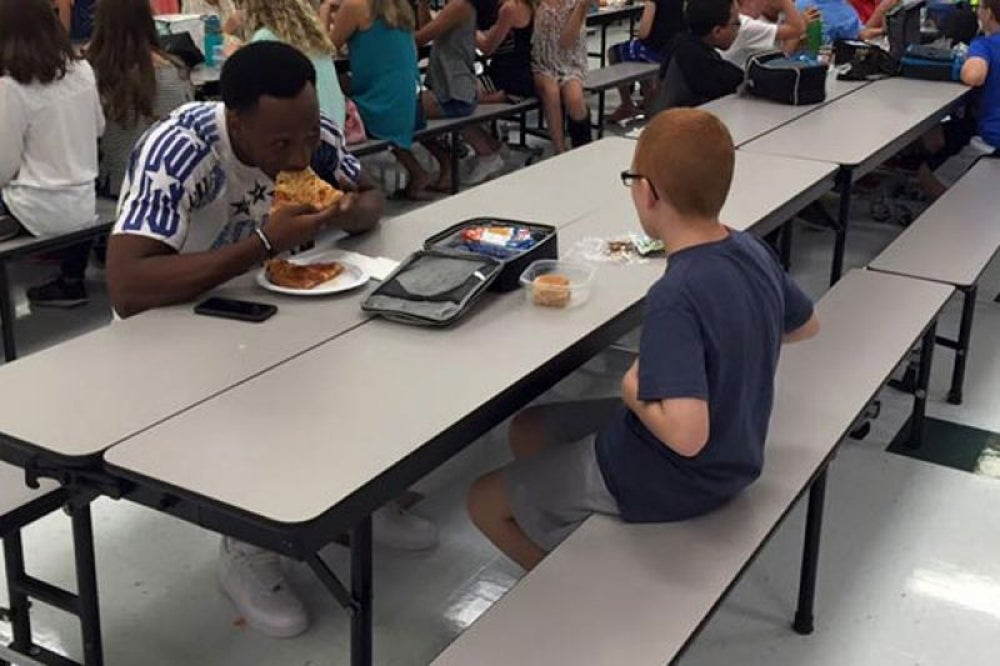 An FSU football player sits with an autistic boy for lunch.