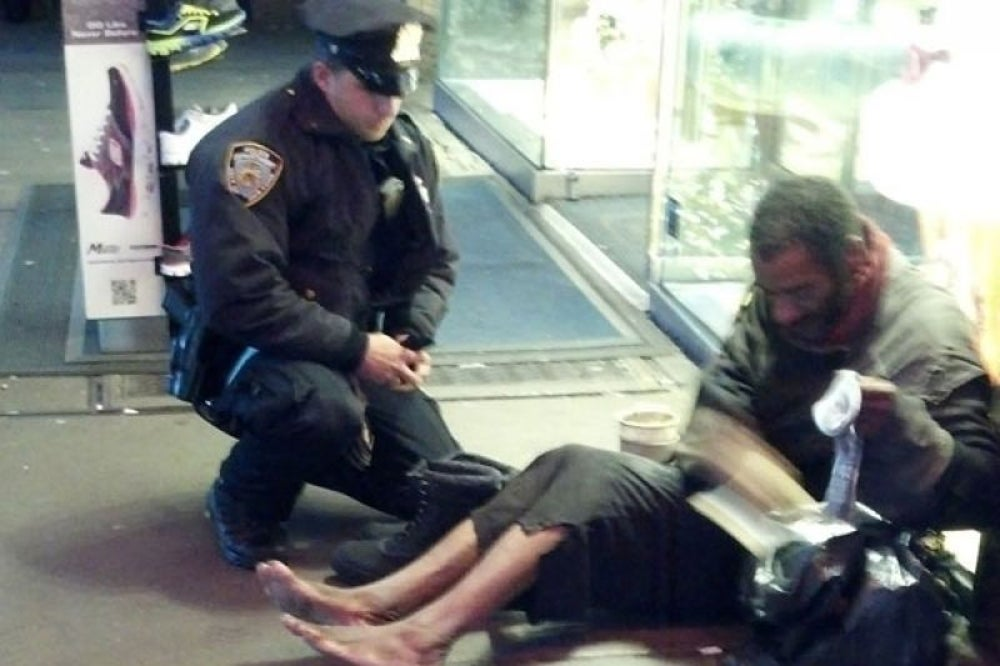 A police officer gives his shoes to a freezing homeless man.