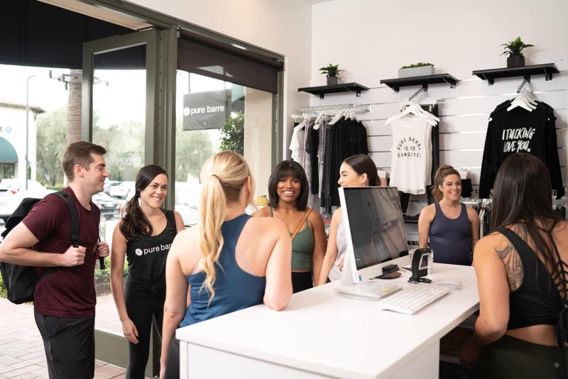 Pure Barre - Group gathering and talking at the Pure Barre check-in counter.