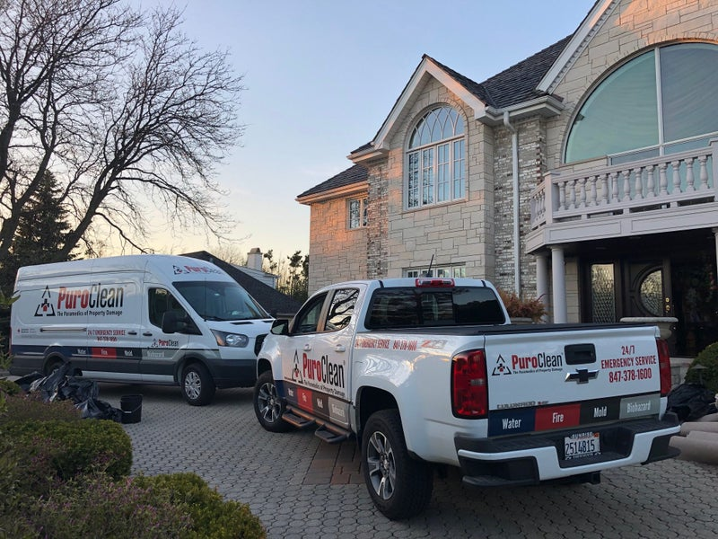 PuroClean trucks in front of a home