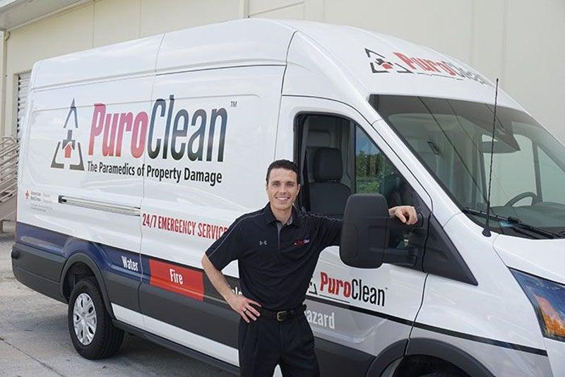 PuroClean employee next to van