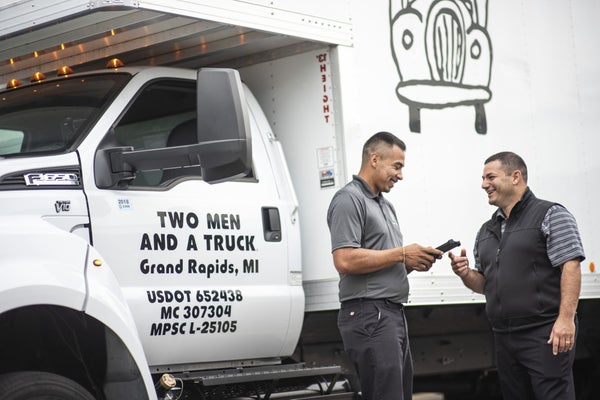 Two men standing in front of a truck